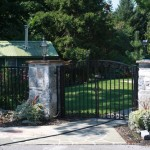 Close up view of curved top black aluminum gate with stone columns and landscaping
