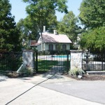 Curved top black aluminum double gate entrance with stone columns