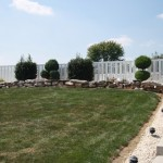 Entire yard view with landscaping in front of white vinyl fence