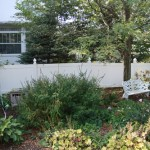Landscaped area in front of white vinyl fence